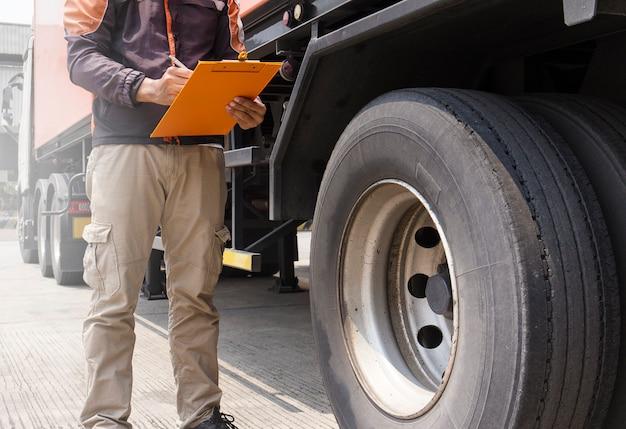 Motorista de caminhão está segurando uma prancheta com inspecionar um pneu de caminhão.