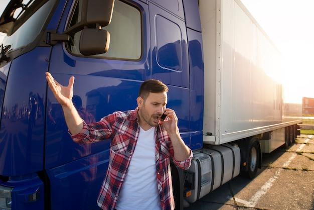 Motorista de caminhão falando ao telefone e discutindo na frente do trailer do caminhão.