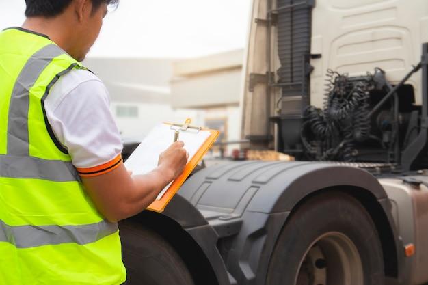 Motorista de caminhão, inspecionando a lista de verificação diária de segurança, o caminhão semi