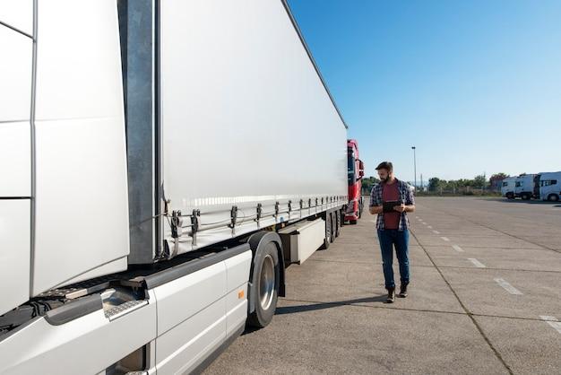 Motorista de caminhão inspecionando veículo, trailer e pneus antes de dirigir