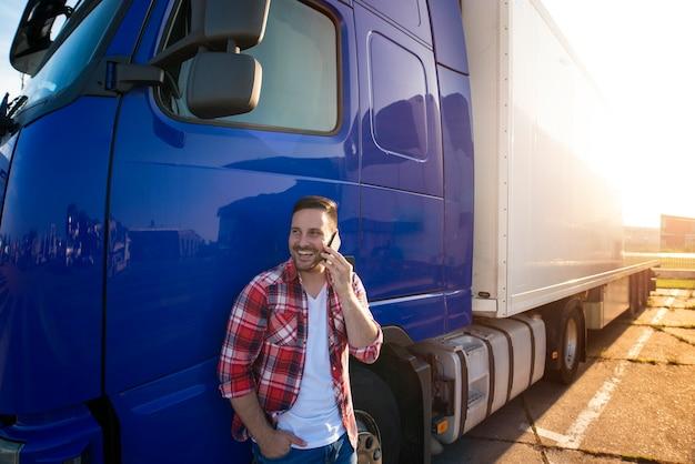 Motorista de caminhão parado ao lado de seu caminhão e falando ao telefone.