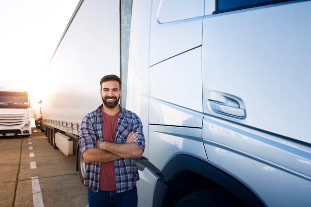 Motorista de caminhão profissional com os braços cruzados em um veículo semi-caminhão.