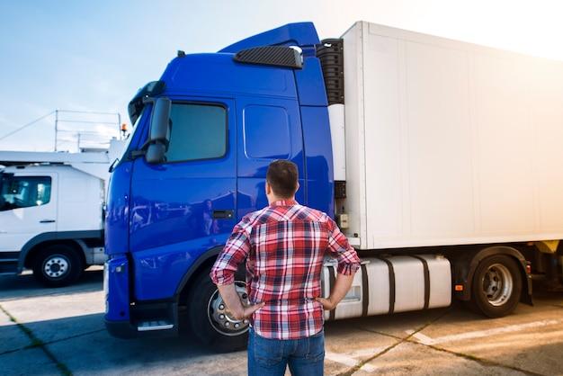 Motorista de caminhão profissional de meia idade em roupas casuais, olhando para o veículo do caminhão e indo para uma longa viagem de transporte.