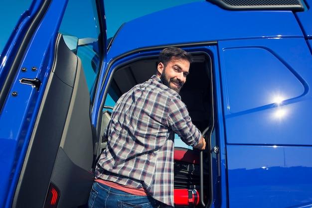 Motorista de caminhão profissional entrando em seu caminhão e pronto para o passeio