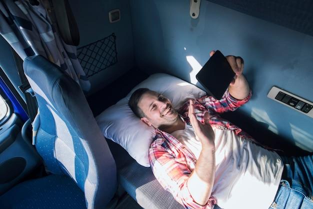 Motorista de caminhão separado de sua família deitado no chão de sua cabine e acenando para sua esposa e filhos por meio de um tablet