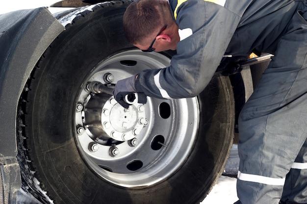 Motorista de caminhão usando chave inglesa para reparo de pneus.