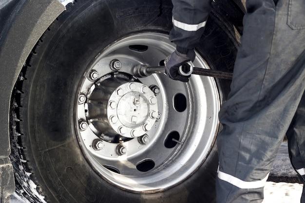 Motorista de caminhão usando chave para reparo de pneus.