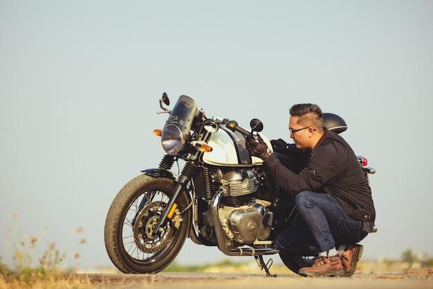 Motorista de capacete e jaqueta de couro está parado na estrada ao lado de uma motocicleta esportiva