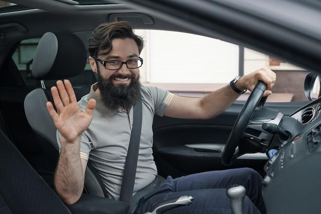 Motorista de carro feliz com cinto de segurança apertado acenando