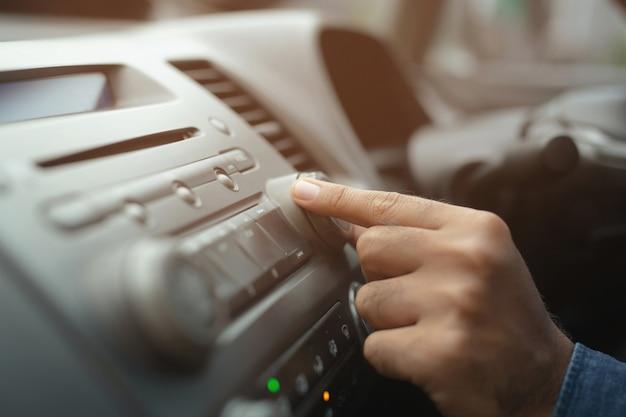 Motorista de carro mudando o botão de giro estações de rádio em seu veículo