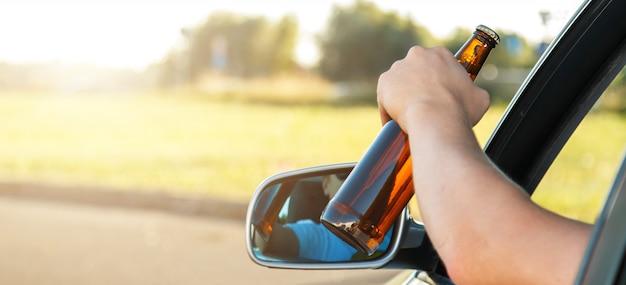 Motorista de carro segurando uma garrafa de cerveja