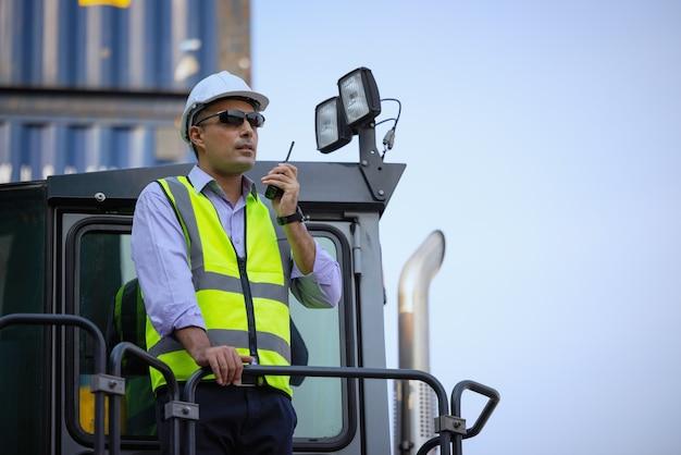 Motorista de construção com escavadeira ao ar livre, gerente industrial