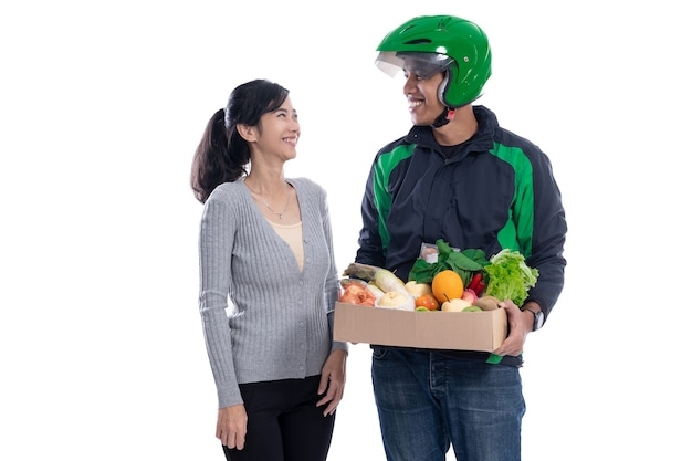 Motorista de correio com comida enviando pedido online para cliente isolada no branco