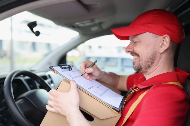 Motorista de correio sorridente no carro com documentos e caixa