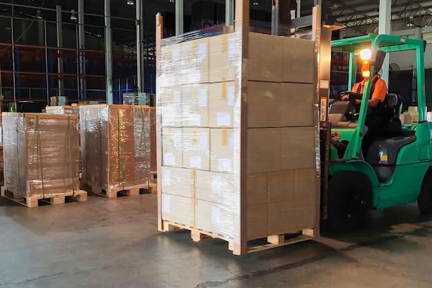 Motorista de empilhadeira carregando mercadorias de paletes de remessa pesada em armazém