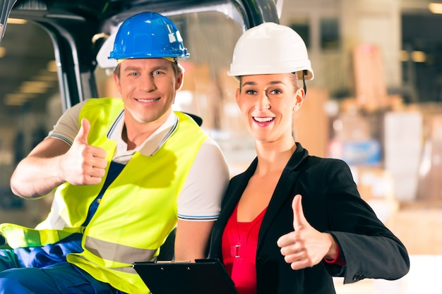 Motorista de empilhadeira e super viseira feminina com prancheta no armazém da empresa de agenciamento de carga, polegares para cima