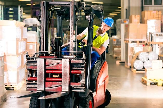 Motorista de empilhadeira em colete protetor dirigindo empilhadeira no armazém da empresa de expedição de mercadorias