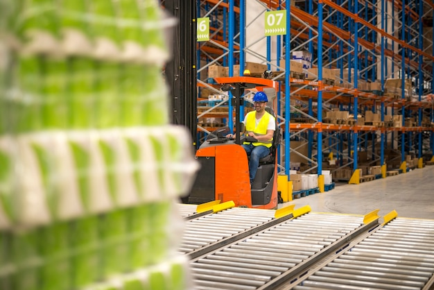 Motorista de empilhadeira manuseando mercadorias em um grande centro de distribuição de armazém.