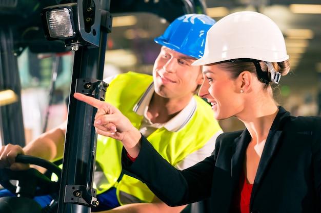 Motorista de empilhadeira no armazém da empresa de encaminhamento de frete, super viseira feminina ou colega de trabalho, apontando