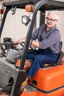 Motorista de empilhadeira sênior sério de óculos carregando mercadorias das entregas na fábrica