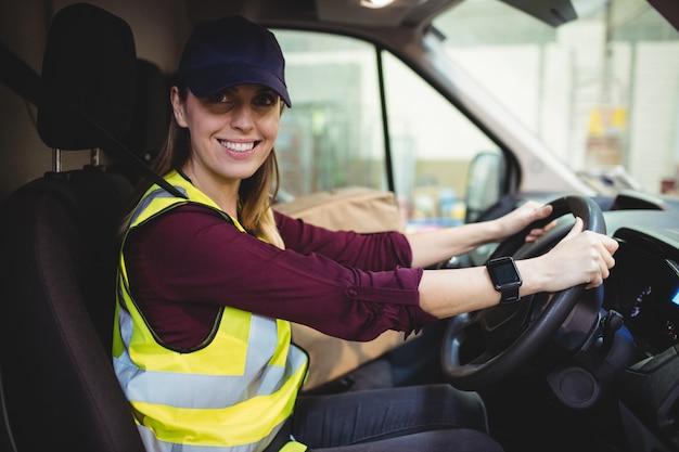 Motorista de entrega, dirigindo a van com parcelas no banco fora do armazém