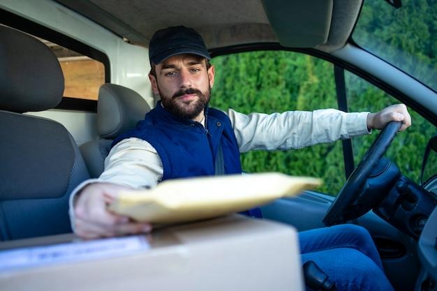 Motorista de entrega dirigindo van com pacotes no assento fora do armazém para o cliente.