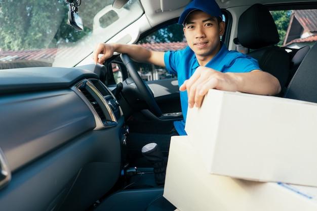 Motorista de entrega que conduz o carro com pacotes no assento fora do armazém.