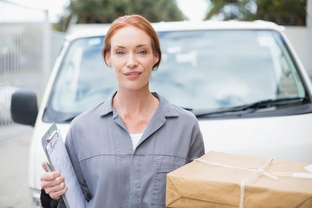 Motorista de entrega sorrindo para a câmera por sua van segurando parcela