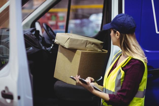 Motorista de entrega, verificando sua lista na área de transferência em um grande armazém