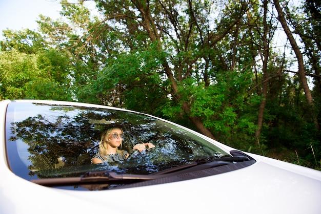 Motorista de garota atraente e alegre se senta no banco do motorista de um carro moderno.