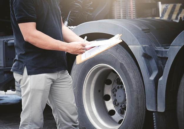 Motorista de mecânico de automóveis segurando a prancheta está verificando as rodas de um caminhão e inspeção de pneus do caminhão de segurança