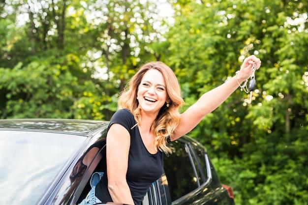 Motorista de mulher segurando as chaves do carro, dirigindo seu novo automóvel rindo jovem.