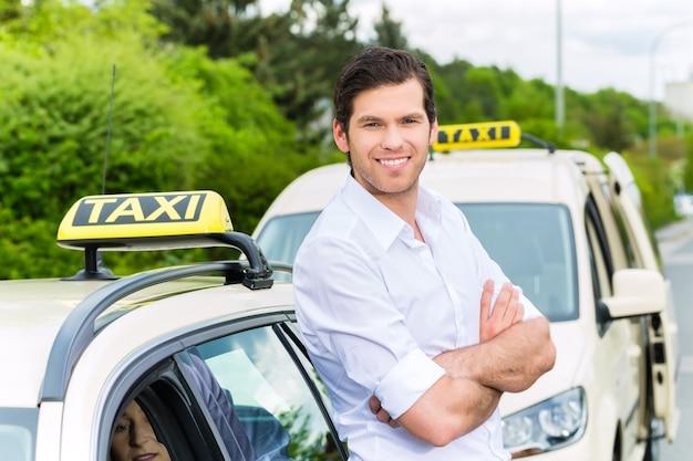 Motorista de táxi experiente na frente de seu táxi, esperando por um passageiro