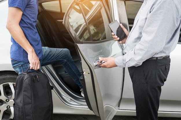 Motorista de táxi que cumprimenta seus passageiros com suas bagagens