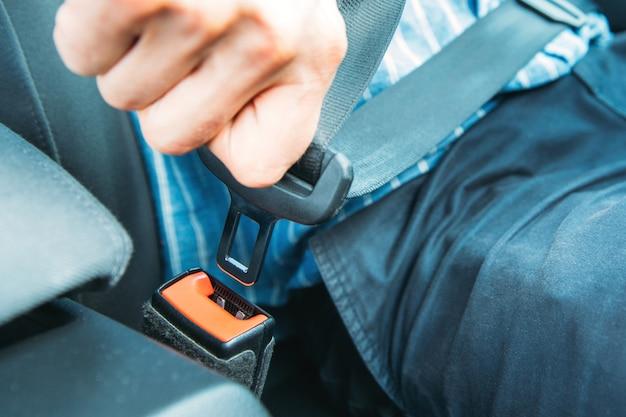 Motorista do homem sentado no banco do carro e fixação / usando cinto de segurança