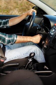 Motorista do sexo masculino mãos começando um carro