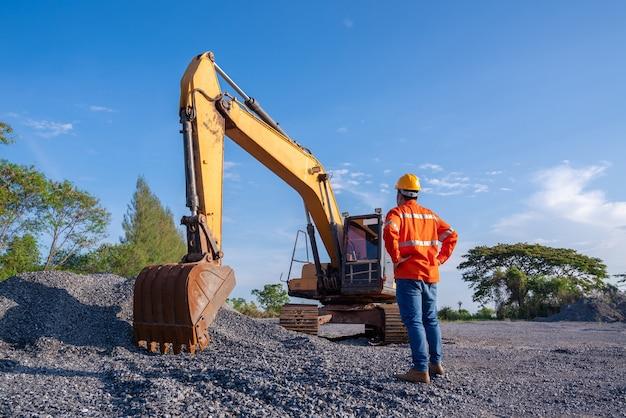 Motorista e escavadeira para construção de estradas no canteiro de obras.