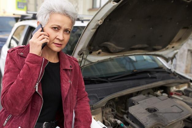 Motorista elegante e atraente de cabelos grisalhos, mulher madura em pé perto de seu carro branco quebrado com o capô aberto e falando ao telefone