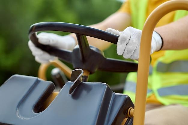 Motorista experiente com mãos enluvadas sentado ao volante