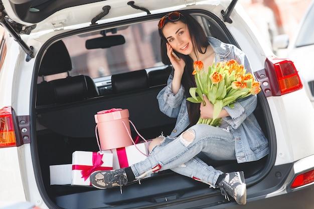 Motorista falando no telefone. menina bonita no carro. senhora dirigindo um carro branco.