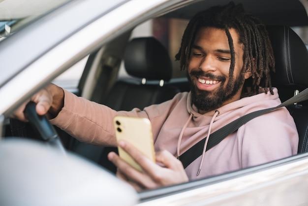 Motorista feliz olhando para o telefone Foto Premium