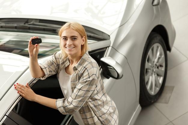 Motorista fêmea feliz nova que sorri guardando as chaves do carro a seu automóvel novo.
