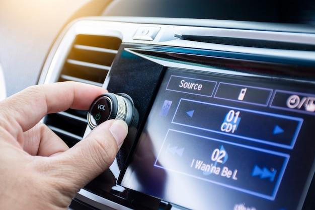 Motorista, girando o botão de volume do auto-rádio