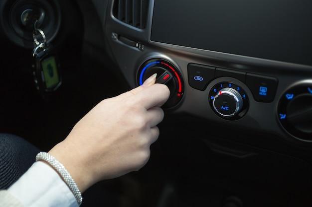 Motorista girando o botão do ar condicionado do carro