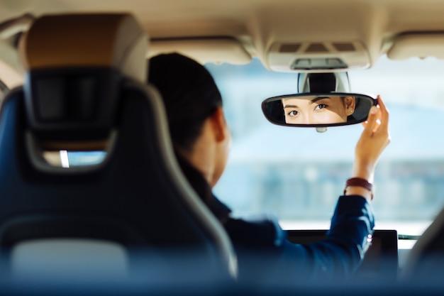 Motorista habilidoso. mulher inteligente e positiva consertando o espelho retrovisor enquanto olha para ele