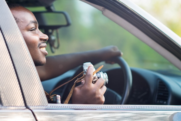 Motorista homem africano segurando uma câmera de filme e sorrindo enquanto está sentado em um carro com a janela frontal aberta.