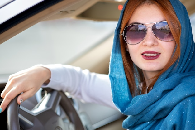 Motorista jovem elegante cachecol e óculos de sol, dirigindo um carro.