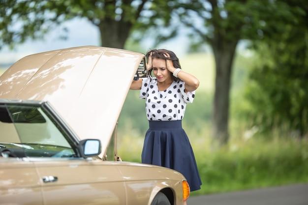 Motorista jovem segurando sua cabeça nas mãos de desespero depois que uma falha no motor parou o carro na natureza.