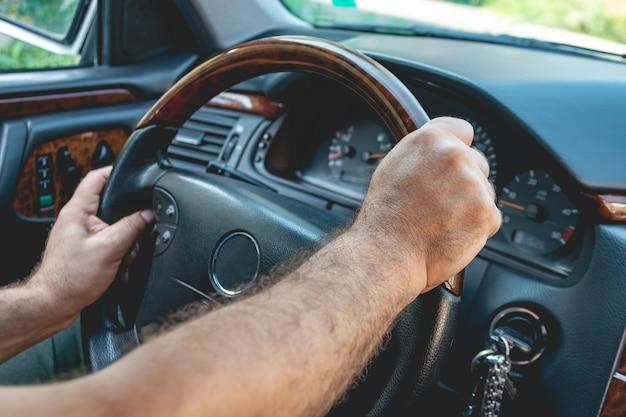 Motorista masculino mãos segurando o volante. homem dirigindo um carro.