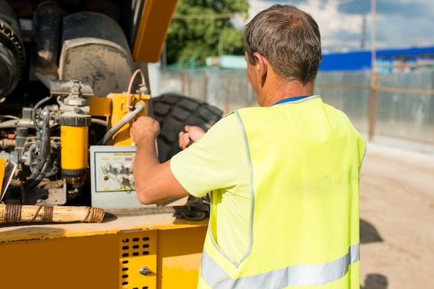Motorista mecânico trocando óleo em um compactador em um canteiro de obras